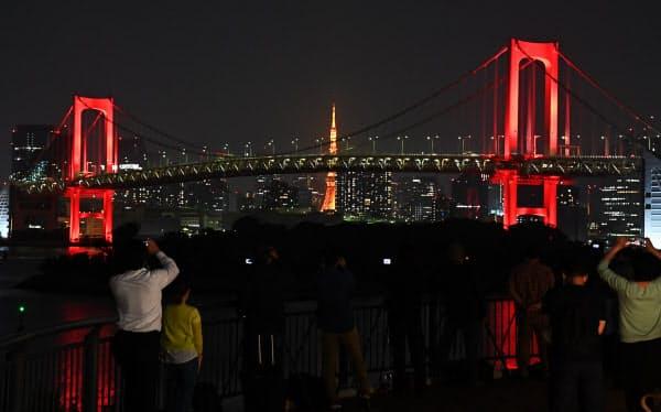 「東京アラート」が発動され、赤色にライトアップされたレインボーブリッジ(2日、東京都港区)