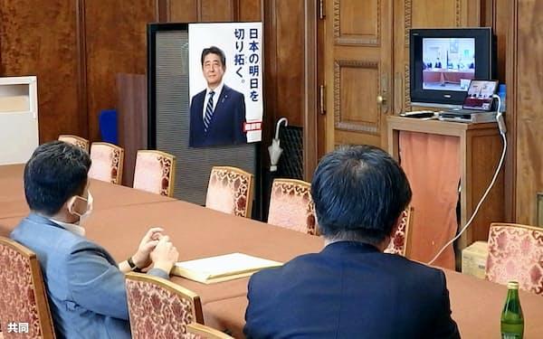 参院議員総会が再開し、テレビ会議システムで幹部のあいさつを聞く自民党議員(3日)=共同