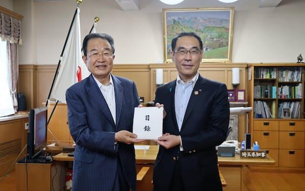 寄付の目録を手渡したヤオコー川野会長(左)と受け取った大野埼玉県知事