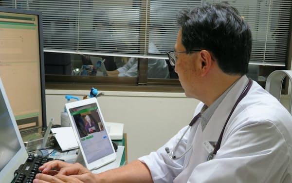医師の山下氏はタブレットで患者の様子を確認する