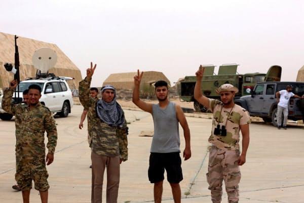 北西部のワティーヤ空軍基地を制圧したシラージュ暫定政権側の戦闘員ら(5月18日)=ロイター