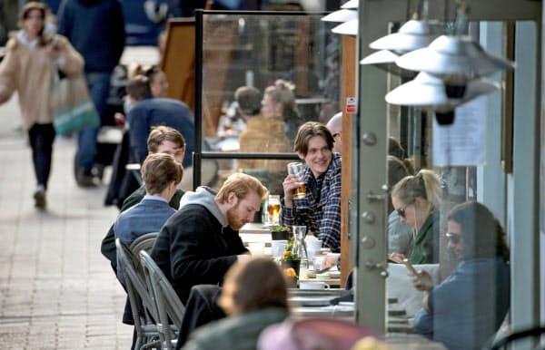 新型コロナウイルスの感染が広がるなか、屋外のレストランで食事を楽しむ人たち(4月、ストックホルム)=ロイター
