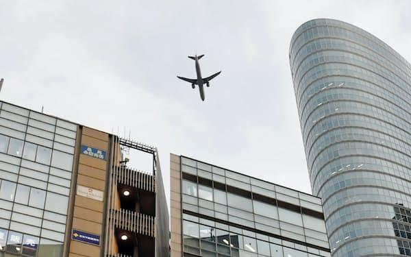 羽田空港の新ルートで、JR品川駅の上空を飛行する旅客機(2月、東京都港区)