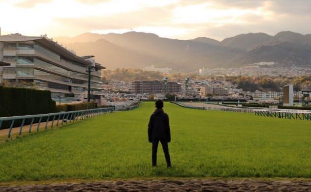 阪神競馬場の芝コース上に立つ吉田歩さん=本人提供