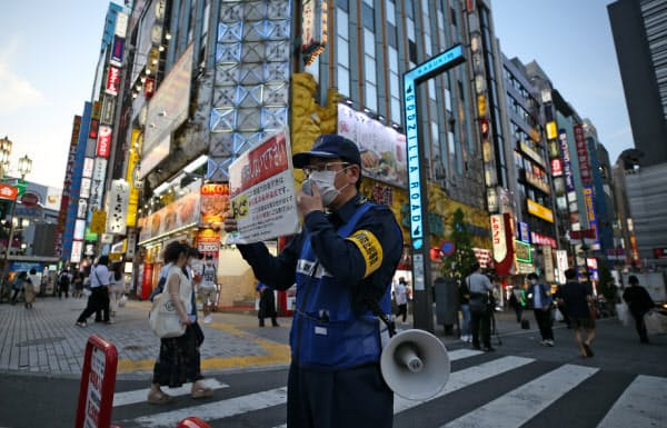 繁華街で感染拡大の警戒を呼びかける東京都新宿区の関係者(4日、同区)