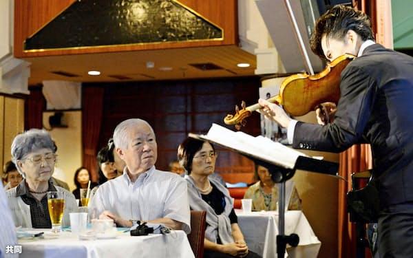 娘のめぐみさんとの再会を願い開かれたコンサートで、バイオリニスト吉田直矢さんの演奏を聴く横田滋さん、早紀江さん夫妻(2014年8月、東京・銀座)=共同