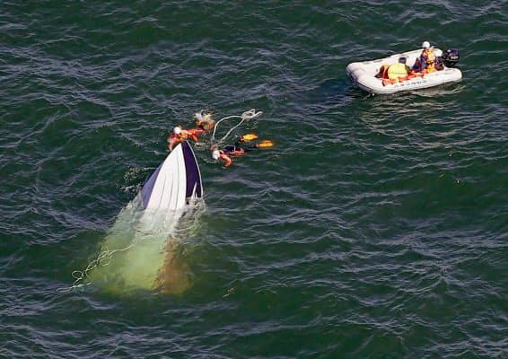 琵琶湖で転覆したクルーザー(左)に近づくダイバー。右は大津市消防局のボート(7日午後3時40分)=共同