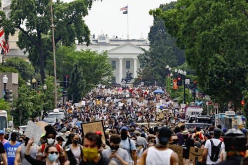 週末に米ホワイトハウス近くで行われたデモには黒人男性が警察官に窒息死させられたことに抗議する大勢の人々が参加した=AP