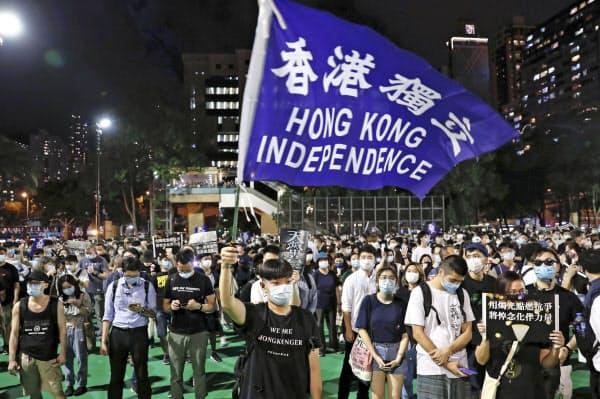 香港のビクトリア公園での天安門事件追悼集会で「香港独立」と書かれた旗を振る参加者=4日(ロイター=共同)