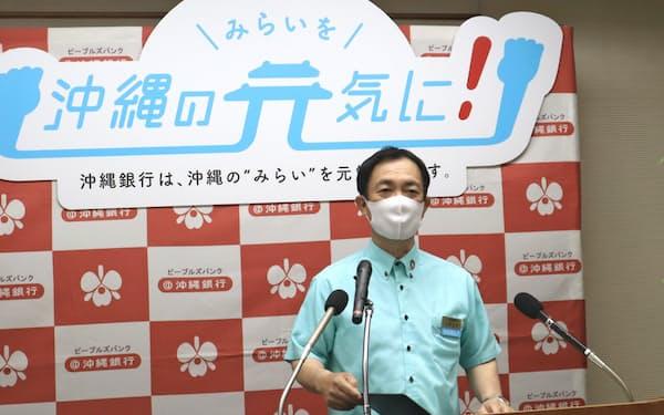 記者会見する沖縄銀行の山城正保頭取(9日、那覇市)
