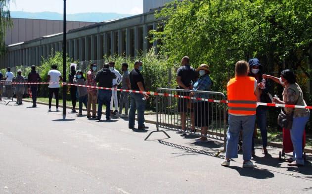 アイスホッケー場に食料配給を求める人の列ができた(5月30日、ジュネーブ)