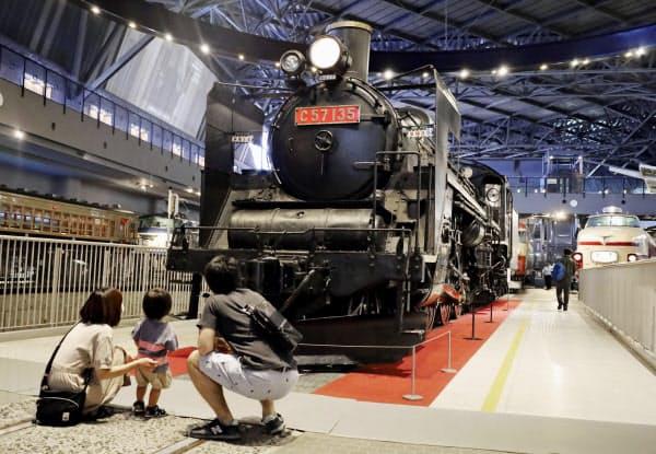 営業を再開した鉄道博物館で、展示されている蒸気機関車を見る親子連れ(10日午前、さいたま市)=共同