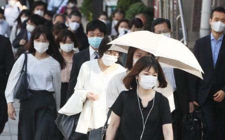 マスク姿で職場などに向かう人たち(13日午前、東京都中央区)