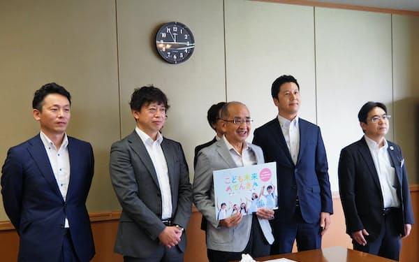 広瀬勝貞知事に取り組みを報告した新電力おおいたの山野健治社長(右端)ら(大分県庁)