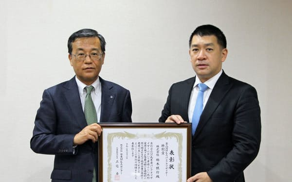 日本M&Aセンターの大槻常務(右)が栃木銀行の猪俣専務に表彰状を贈った(11日、宇都宮市の栃木銀行本店)