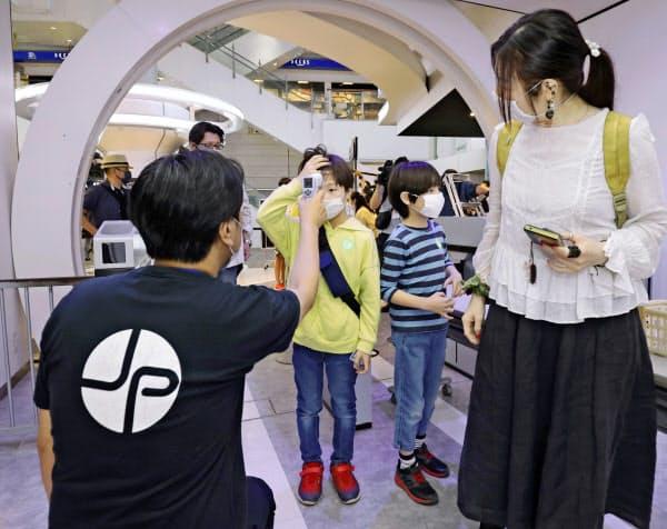 営業を再開した「東京ジョイポリス」で検温を受ける子どもたち(13日午前、東京・お台場)=共同