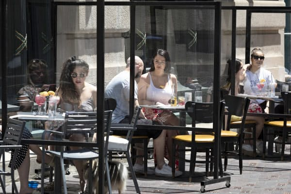 6月12日、米ボストンのレストランでは屋外で食事を楽しむ人たちの姿が見られた。テーブルの間にはシールドが設置されている=AP