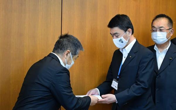 宮城県漁協の丹野会長(左)から要望書を受け取る村井知事(中)(15日、宮城県庁)