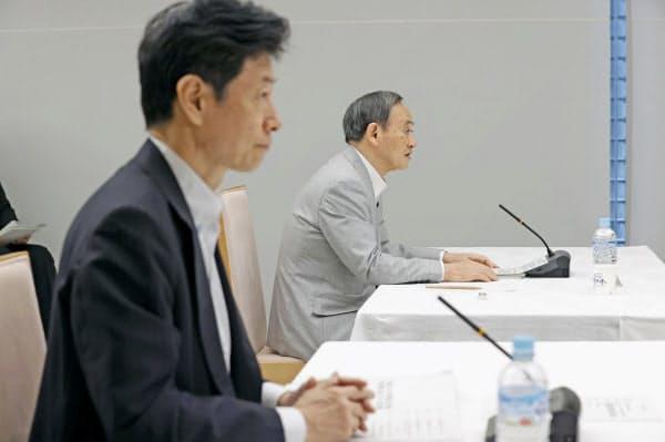 テレビ会議方式で行われたデジタル市場競争会議に臨む西村経済再生相(手前)と菅官房長官(16日午前、首相官邸)=共同