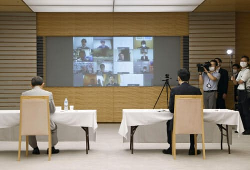 テレビ会議方式で行われたデジタル市場競争会議。左は菅官房長官、右は西村経済再生相(16日午前、首相官邸)=共同