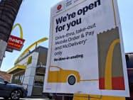 マクドナルドの店舗の多くはまだドライブスルー、持ち帰りなどの営業にとどまっている(5月、ロサンゼルス)=AP