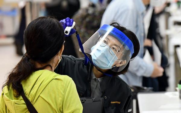 成田空港の検疫所で入国者の検温をする職員(6月5日)