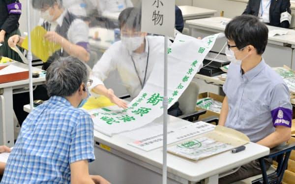 都知事選の立候補受け付けで「7つ道具」を渡す、東京都選挙管理委員会事務局の職員(18日午前、東京都新宿区)
