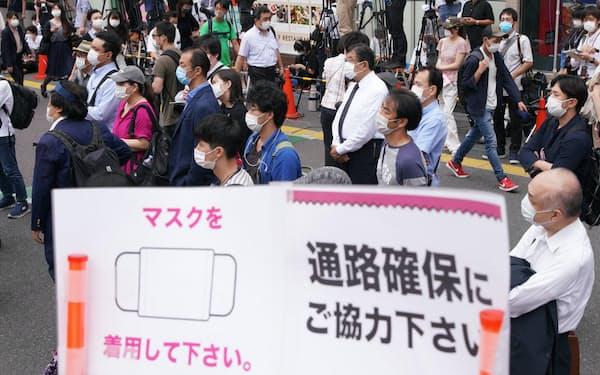 候補者の第一声を聞く有権者(18日午前、東京都新宿区)