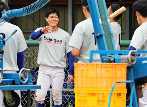 練習でチームメートと話す西部ガス硬式野球部の井手隼斗主将(左端)=福岡市