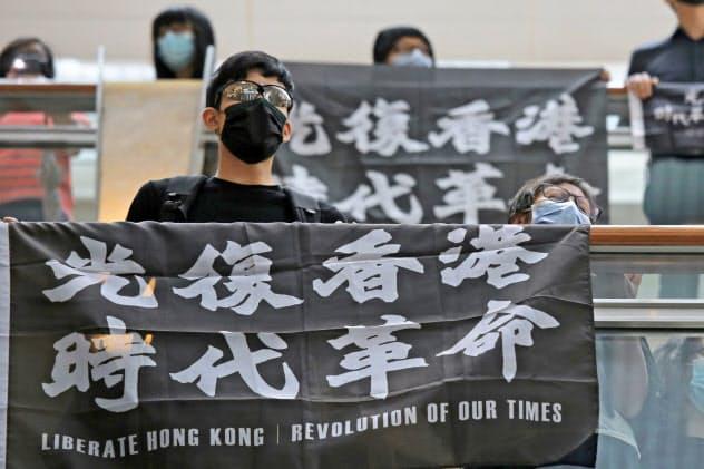 16日、香港で抗議の旗を掲げるデモ参加者=AP
