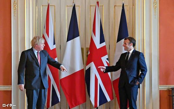 社会的距離に配慮しながら対面したジョンソン英首相(左)とマクロン仏大統領(18日、ロンドンの英首相官邸)=ロイター