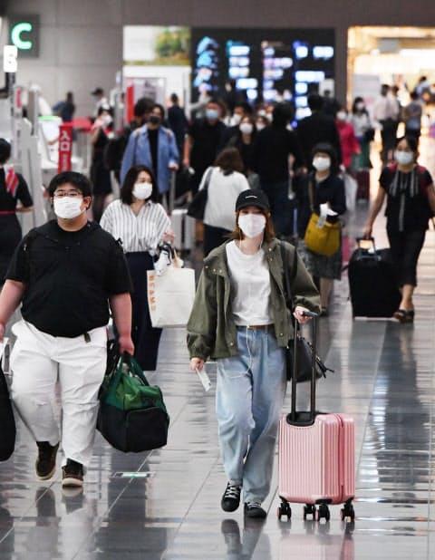 県をまたぐ移動の自粛が解除され、羽田空港から各地へ向かう人たち(19日午前)
