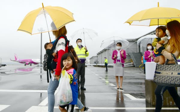 ピーチが国内全線の運航を再開し、スタッフらに見送られながら機体に向かう乗客(19日午前、関西国際空港)