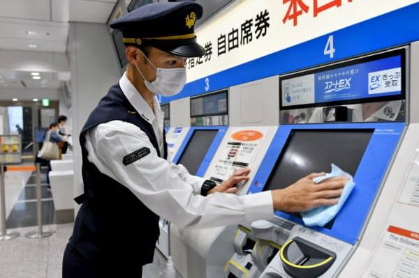 券売機を消毒するJRの職員(19日午前、JR東京駅)