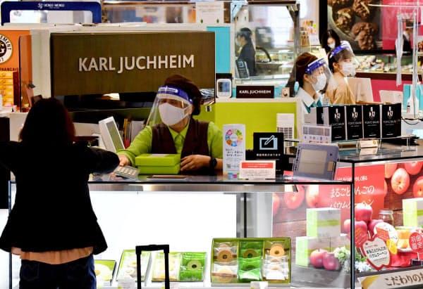 マスクとフェースシールドを付けて接客する店員(19日午前、羽田空港)