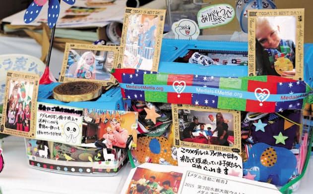 メダルを募集する箱は子どもたちの写真などで装飾されている(大阪市中央区)