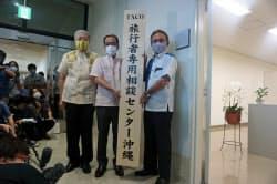 旅行者相談センターの看板を手にする沖縄県の玉城デニー知事(右)(19日、那覇空港)