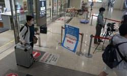 到着口のサーモグラフィーで到着客の体温を測る(19日、那覇空港)