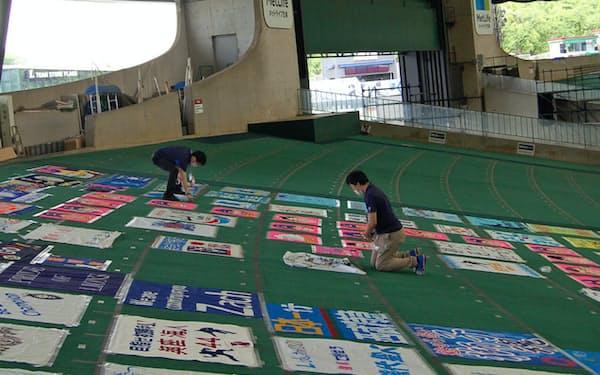 開幕戦を前にファンが寄せたフラッグを外野席に飾る埼玉西武ライオンズの職員(18日、埼玉県所沢市のメットライフドーム)