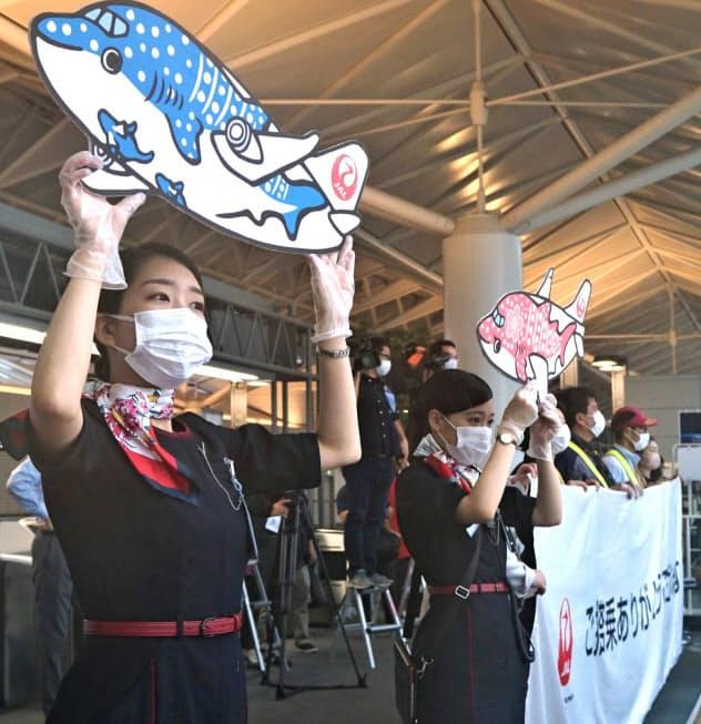 那覇便の搭乗客を見守る日本航空グループの職員(19日、中部国際空港)