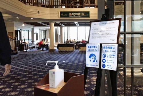 クラブハウス内に設置された消毒液や感染防止を呼びかける掲示板(22日、カメリアヒルズCC)=日本女子プロゴルフ協会提供・共同
