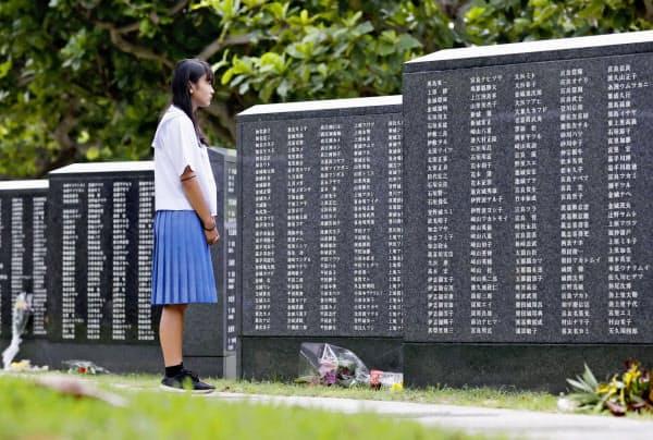 「平和の礎」を見つめる中学生。沖縄戦で曽祖父を亡くした(23日午前、沖縄県糸満市の平和祈念公園)=共同