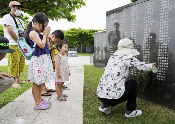 沖縄戦犠牲者の氏名が刻まれた「平和の礎」に手を合わせる家族(23日午前、沖縄県糸満市の平和祈念公園)=共同
