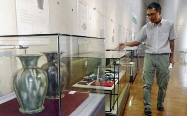 橿原考古学研究所で展示された薩摩遺跡の出土品について説明する北山峰生指導研究員(22日、奈良県橿原市)=共同