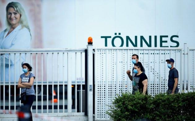 20日、コロナウイルスの集団感染が起きた独食肉処理施設の外を歩く従業員=ロイター