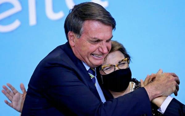 マスクを外すブラジルのボルソナロ大統領(左)(17日、ブラジリア)=ロイター