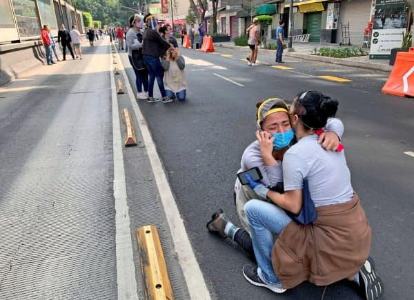 23日、地震発生で道路にしゃがみこむ人(メキシコシティ)=ロイター