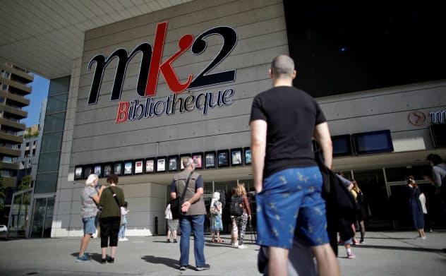 再開されたパリの映画館の前で、ソーシャルディスタンスをとりながら上映を待つ人たち=ロイター