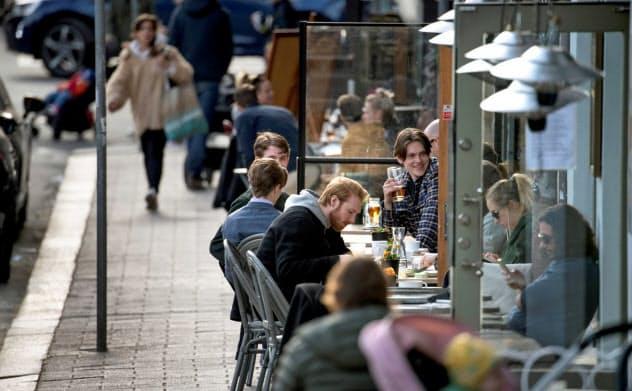都市封鎖されていないスウェーデンの首都ストックホルムのレストランで人々は食事を楽しむ=ロイター