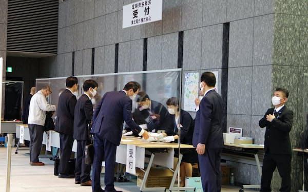 25日、東北電力の株主総会に出席するため、透明なパーテーションで区切られた受付に並ぶ株主ら(仙台市)